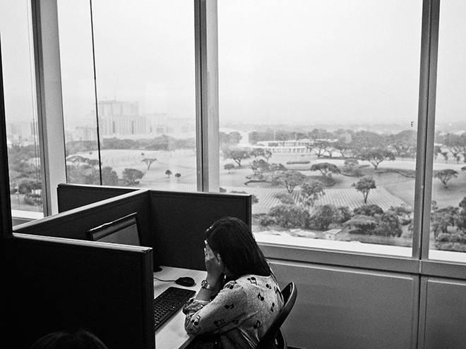Manila, Philippines. August 28, 2014. An employee working as a content moderator for Task Us sits in front of her computer at her cubicle on the 11th floor of the SM Aura Office Building Tower in the Taguig district of Manila. Task Us is an American outsourcing tech company with offices in the Philippines. (Photo by Moises Saman/MAGNUM)